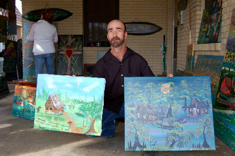 Hank Holland displays his first piece on the left and his latest piece on the right.